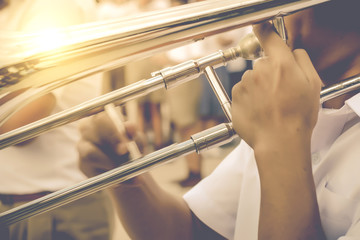 Trombone player in white shirt blowing in marching band.