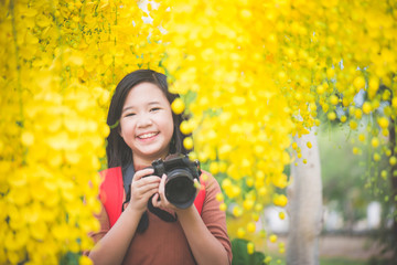 Asian girl take photo with blooming yellow flower