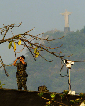 ARMY SOLDIER WATCHES MOVEMENT WITH CORCOVADO MOUNTAIN IN BACKGROUND AT SUMMIT.