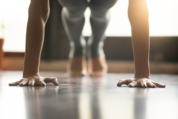 Young woman practicing yoga, doing Push ups or press ups exercise, phalankasana Plank pose, working out, wearing sportswear, grey pants, indoor, home interior, living room floor. Close-up of hands