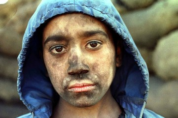 Amrulla, aged 12, takes a few moments rest from his job collecting loose charcoal to be put into sac..