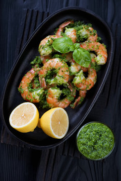 Tiger shrimps with parsley sauce and lemon in a frying pan over black wooden background, studio shot