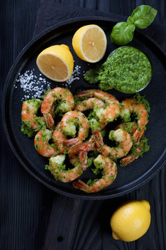 Metal plate with tiger shrimps with chimichurri sauce and lemon, view from above, vertical shot