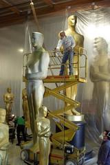 Scenic artist Rick Roberts (C) applies a fresh coat of gold paint to a twenty-five foot tall Oscar p..