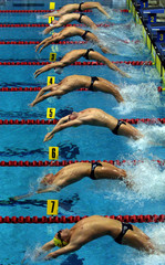 Swimmers of the men's final 100 metres backstroke at the Commonwealth Games in Kuala Lumpur leap off..