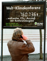 A man uses his mobile phone in front of a digital display showing the worlwide CO2 emissions since t..