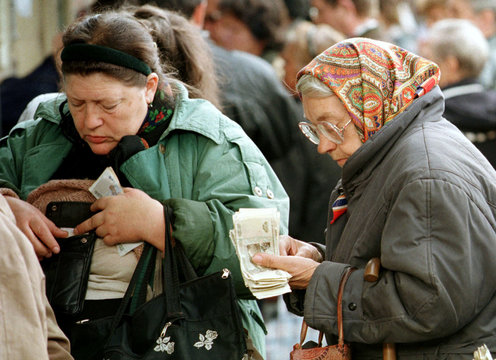 A Russian woman (L) pulls money out of her wallet hidden under a sweater as a babushka counts her mo..