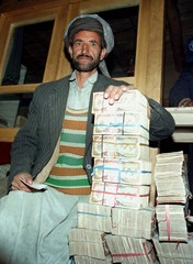 An Afghan farmer sits happy with a heap of Afghan banknotes he received for potatoes sold to the U.N..