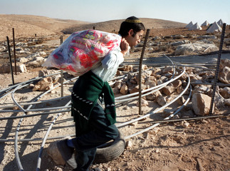 An Israeli settler carries loaves of bread through an obstacle course at the entrance to this 'outpo..