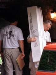 Federal agents carry out boxes designed for guns July 31 from the house of Olympic Centennial Park b..