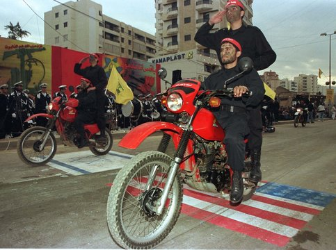 PRO IRANIAN HIZBOLLAH MILLITANTS RIDE MOTORCYCLES OVER AMERICAN FLAG.