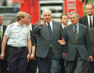 German Chancellor Helmut Kohl (C) walks towards the scene of the wrecked German high-speed train in ..