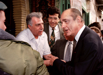 French President Jacques Chirac tells an Israeli soldier to get out of his way as he tries to talk w..