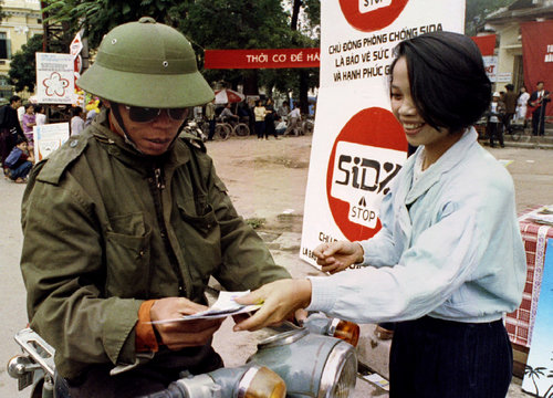 A Hanoi resident receives free condoms and brochures from a government health worker (R) on the eve ..