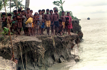 A group of children gather on the banks of the river Padma whose currents washed away the homes of m..