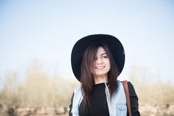 Portrait of beautiful young woman in hat with sun light