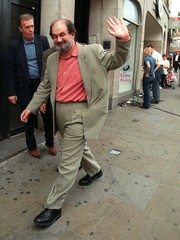 Author Salman Rushdie waves to waiting reporters in the street after a news conference in London Sep..