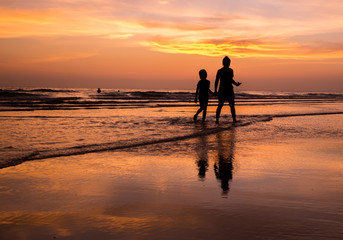silhouette of mother and child  walking on the tropical beach  sunset background