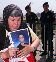 A woman with a picture of her dead son walks past Turkish police during a gathering of family member..