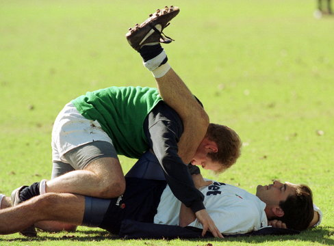 Britain's Nick Greenstock has his leg muscle stretched by teammate Matt Allen (L) after a team pract..