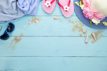 Sun glasses with beach shoes and beautiful hat beach,towel on wooden background.