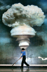 A worker mops the floor in front of a huge picture showing a mushroom cloud on display at Beijing's ..