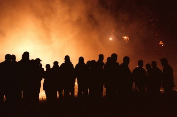 Police floodlights and fireworks illuminate Orangemen at the barbed-wire fence erected to keep them ..