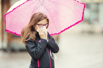 Young girl with flu blowing her nose with a tissue paper under spring rain. Pre-teen girl sneezing and wearing warm clothes against cold weather. Depression, illness allergy under rain.