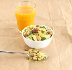 Indian traditional and popular snack, poha chivda, made from frying items like thin flattened rice, red chili, curry leaves, groundnuts, cashew nuts and almonds, and mango juice.