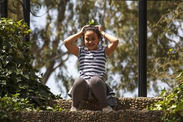 Niña morena rizosa jugando y danzando en el parque