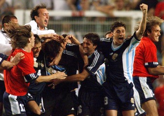 Argentine players mob goalkeeper Carlos Roa (3-L) after he stopped [England's David Batty's penalty ..