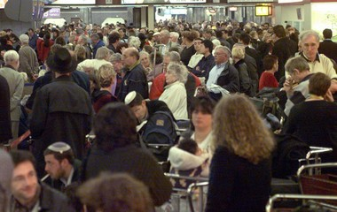PASSENGERS WAIT TO CHECK IN AT AIRPORT WHERE FLIGHTS WERE DELAYED BY PUBLIC WORKER STRIKE.