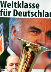 A musician plays in front of a poster which says `World Class for Germany` during an election rally ..