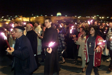 CHRISTIANS IN MILLENNIUM TORCH MARCH ON MOUNT OF OLIVES PAST WALLED OLD CITY.