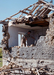 A CHECHEN MAN CLEANS UP THE DEBRIS OF HIS HOUSE.
