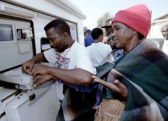A bank operator takes the fingerprint of a South African pensioner at a mobile cash dispenser in thi..