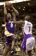LAKERS BRYANT DRIVES TO HOOP OVER RAPTORS BROWN IN NBA ACTION.