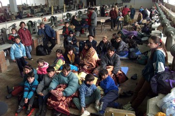 - A group of  ethnic Albanian refugees sit camped in a  factory in Rozaje March 31. The U.N. High Co..