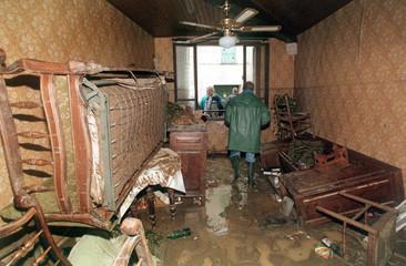 FRENCH INHABITANTS WALK INSIDE THEIR FLOODED HOUSE.