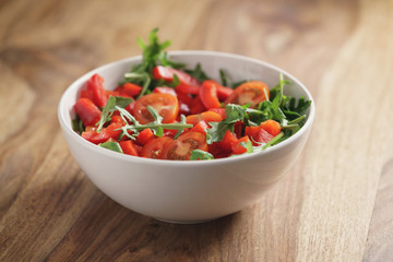 cherry tomatoes with arugula salad in white bowl on wooden table