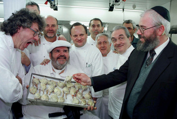 Rabbi Yosef Fink (R) holds a piece of roasted quail before it goes into the oven as he jokes with so..