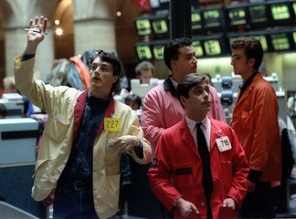A trader (L) receives orders during early trading on the Paris stock exchange, October 18th..