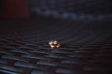 Two wedding rings laying on the dark table