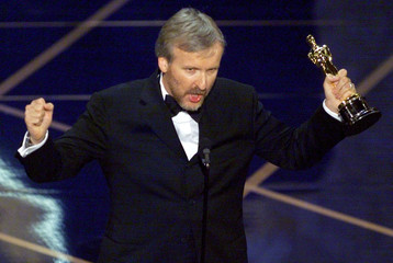 James Cameron holds up the Oscar he won in the of Best Picture for the movie Titanic March 23. Camer..