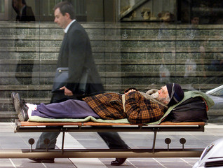 A businessman walks past a homeless man sleeping in a bus-shelter in the centre of Sydney. Social co..