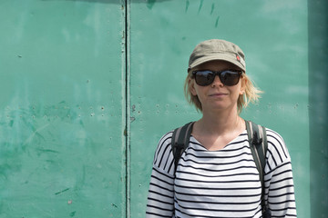 Lady in Striped Shirt, Sunglasses, and Hat with a Backpack