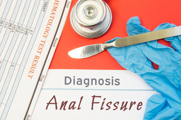 Surgical diagnosis of Anal Fissure. Surgical medical instrument scalpel, latex gloves, blood test analysis lie close beside text inscription diagnosis of Anal Fissure. Concept for surgical diseases