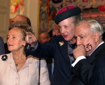 Denmark's Queen Margrethe II (C) explains a design element to Speaker of the French Senate Christian..