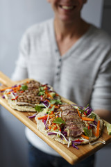 man holding a wooden cutting board with torillas with meat and vegetables