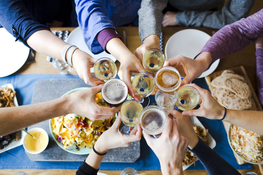 group of friends toasting with beers and wine over dinner